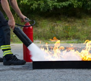 16872142 - instructor showing how to use a fire extinguisher on a training fire
